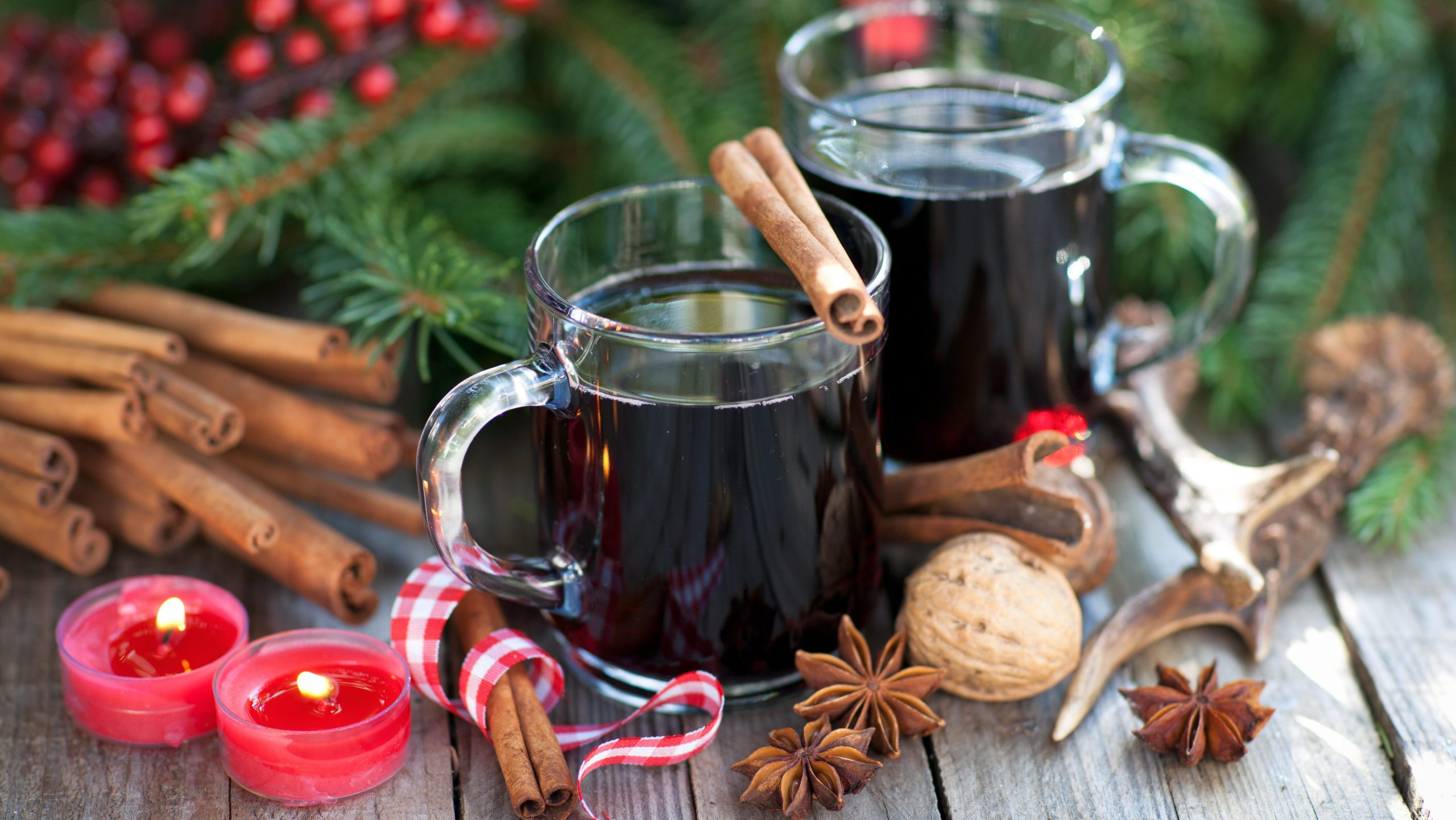 Gläser mit Glühwein auf weihnachtlich geschmücktem Tisch