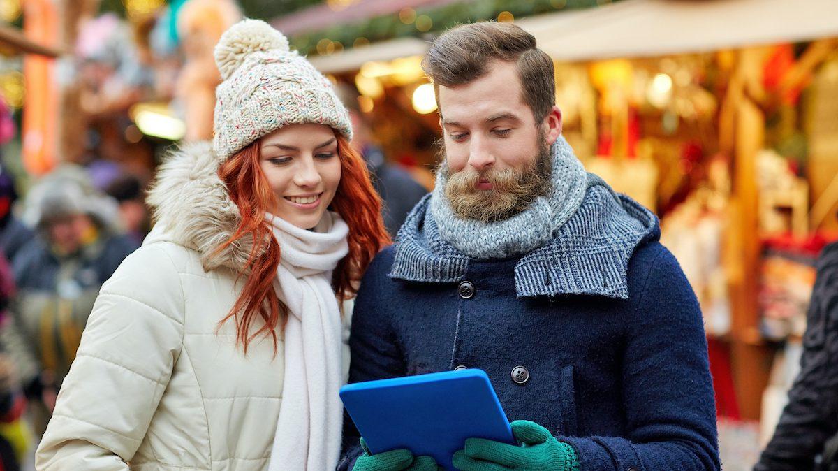 Paar mit iPad in der Hand vor einem Stand auf dem Weihnachtsmarkt